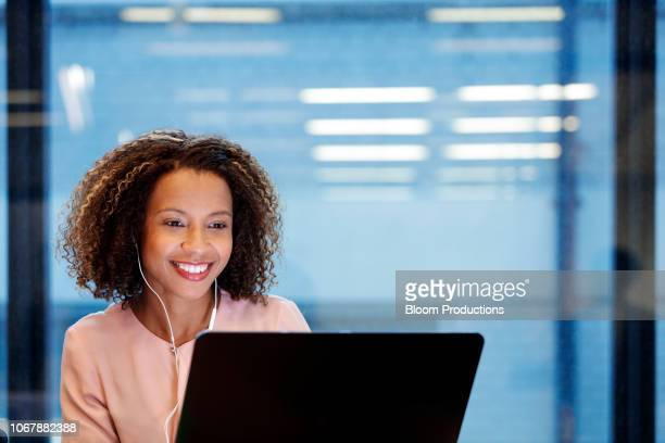 young smiling businesswoman wearing earphones, using laptop - social media stock photos and pictures
