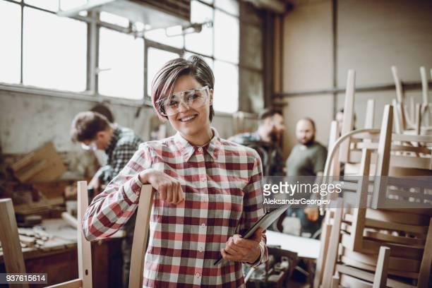 jovem sorrindo carpinteiro em frente de trabalhar equipe em sua oficina - pequeno - fotografias e filmes do acervo