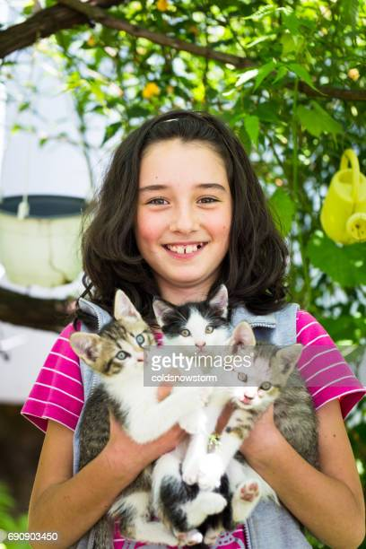 Young smiling caucasian girl outdoors holding three cute kittens
