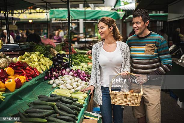 Young smiling couple buying groceries together on farmer's market.