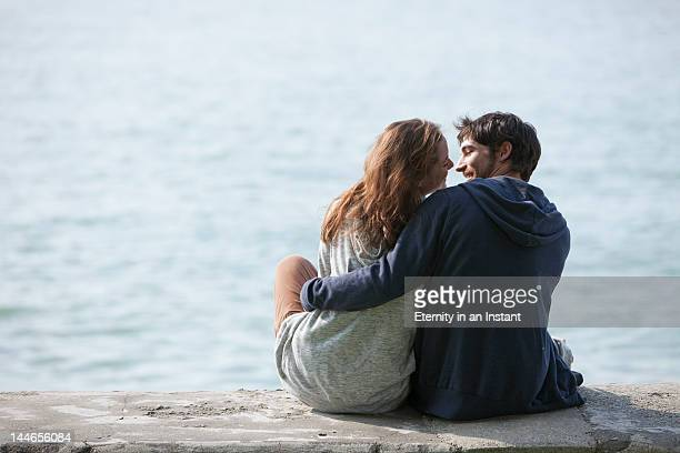 young smiling couple hugging outdoors - water's edge stock pictures, royalty-free photos & images