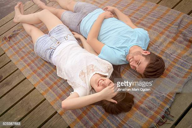 Young smiling couple lying on blanket on jetty