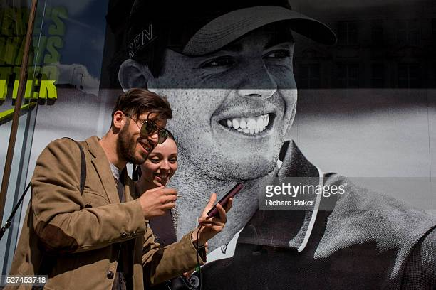 Young smiling couple pass a Nike retail poster of Northern Irish golfer Rory McIlroy in central London The young woman seems delighted with her...
