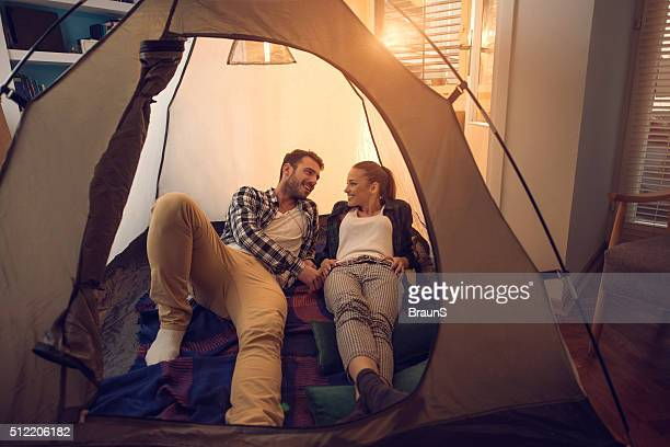 Young smiling couple relaxing in a tent at home.