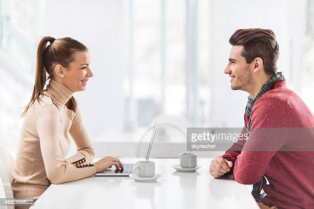 Young smiling couple talking in cafe.