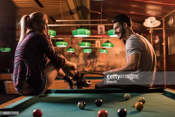 Young smiling couple talking to each other in pool hall.