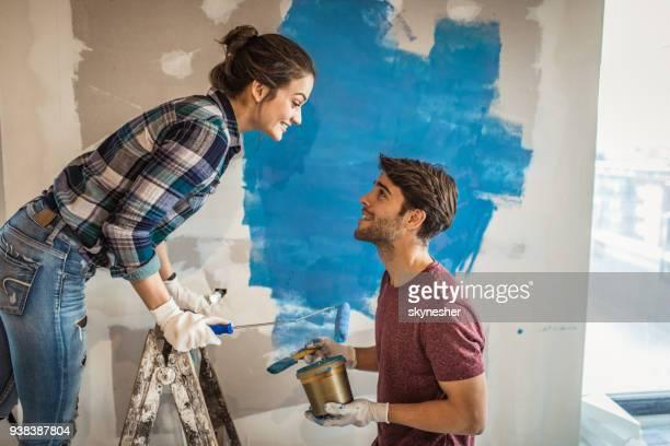 junges lächeln paar talking beim renovieren ihrer wohnung. - renovierung konzepte stock-fotos und bilder