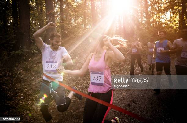 Young smiling couple winning marathon race in the forest while crossing finish line together.
