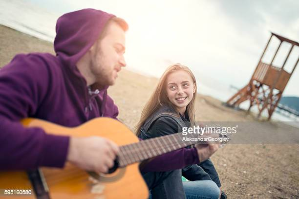 Young Smiling Couple with Acoustic Guitar Singing at Beach Party