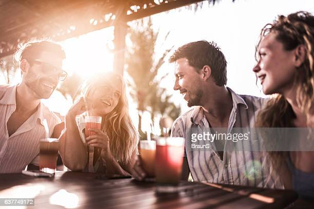 Young smiling couples relaxing in a bar and communicating.