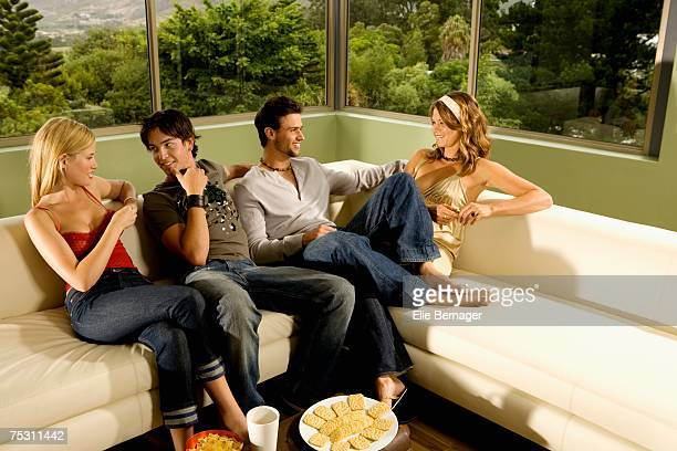 2 young smiling couples talking, sitting on sofa