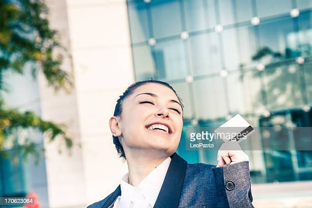Young smiling executive holding a white credit card