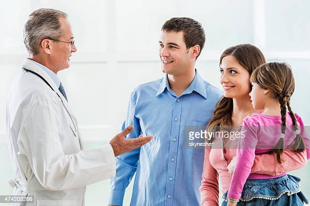 Young smiling family communicating with a mature doctor.