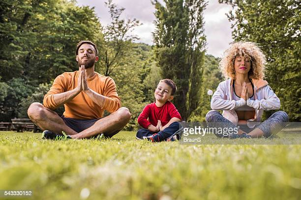 Young smiling family doing Yoga relaxation exercises on a grass.
