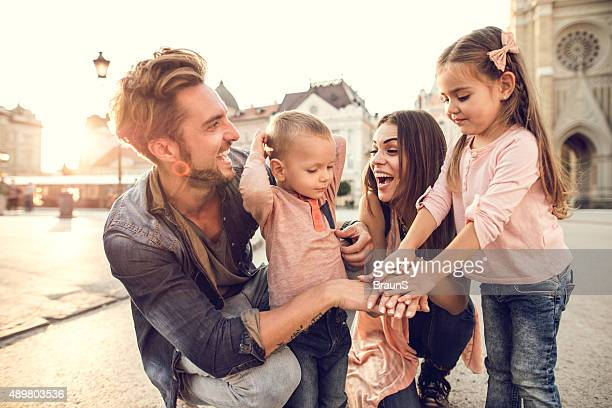 Young smiling family joining their hands in the city.