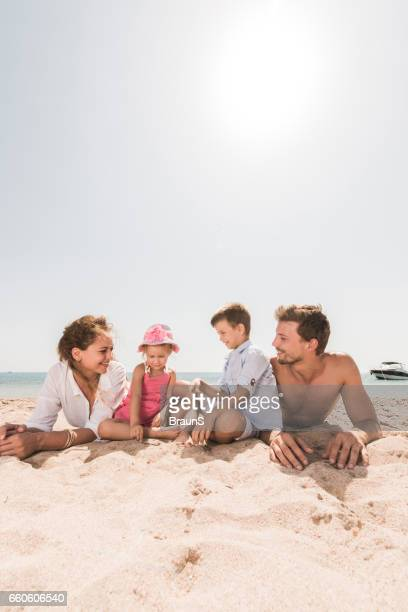 Young smiling family relaxing in sand on the beach.