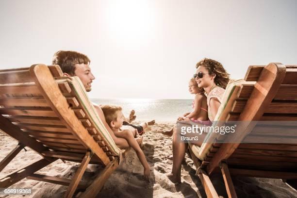 Junge, lächelnde Familie auf Liegestühlen entspannen und kommunizieren.