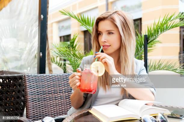 Jeune fille souriante, boire un cocktail savoureux, plein air