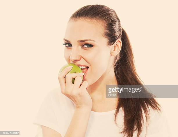young smiling girl eats a green apple