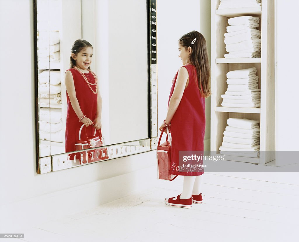 Young, Smiling Girl Looking at Her Reflection in the Mirror : Stock Photo