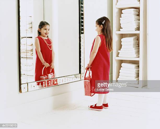young, smiling girl looking at her reflection in the mirror - girl in mirror stock-fotos und bilder