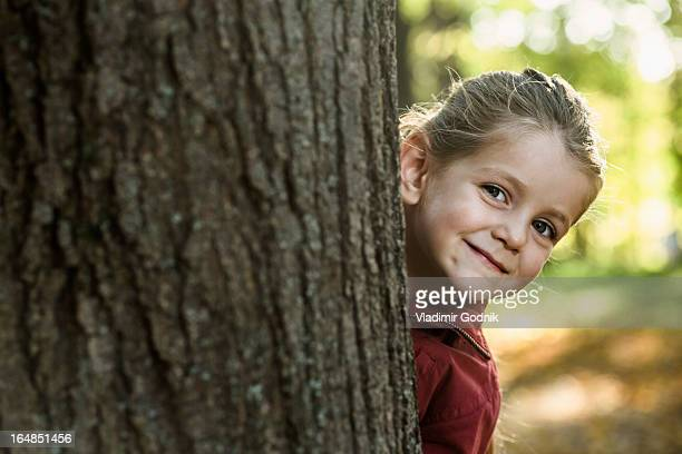 A young smiling girl peeking from behind a tree trunk