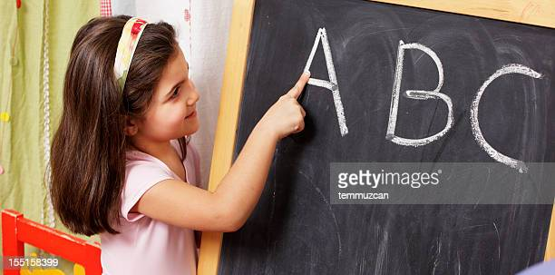 Young smiling girl pointing to letters on a chalkboard.