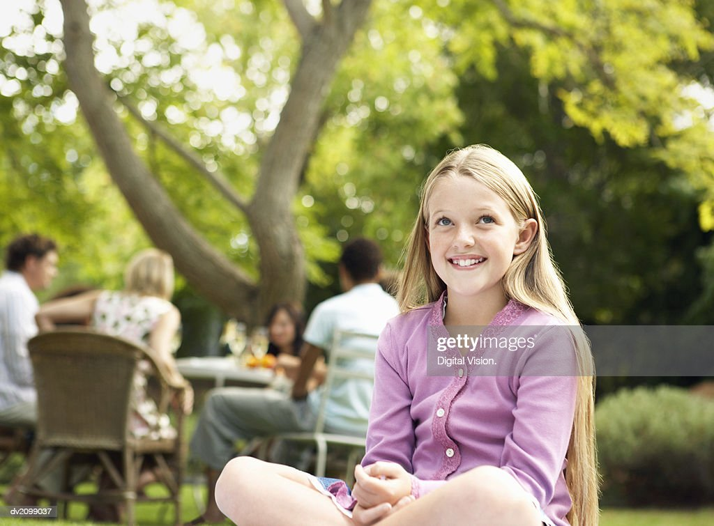 Young Smiling Girl Sits Cross-Legged in a Garden, People at a Table in the Background : Stock Photo