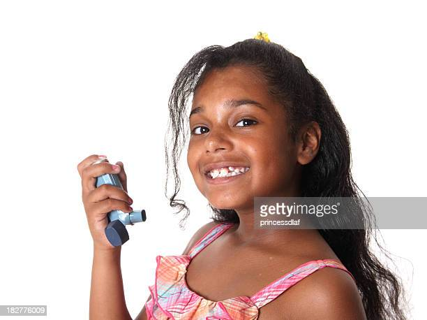 Young smiling girl with an inhaler in her hand