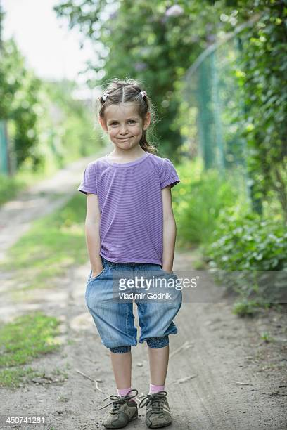 A young smiling girl with hands in her pockets, standing on a dirt road