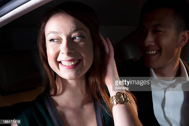 Young smiling, happy, couple sitting in their car and arriving at a red carpet event at night in Beijing