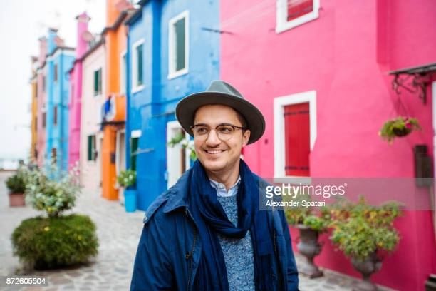 Young smiling happy man in glasses and hat among colorful houses of Burano, Italy