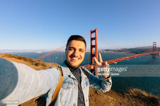 young smiling happy man taking selfie at golden gate bridge in san francisco, california, usa - north america stock pictures, royalty-free photos & images