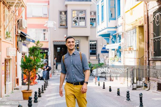 young smiling happy man walking on the street in istanbul, turkey - pedestrian zone stock pictures, royalty-free photos & images
