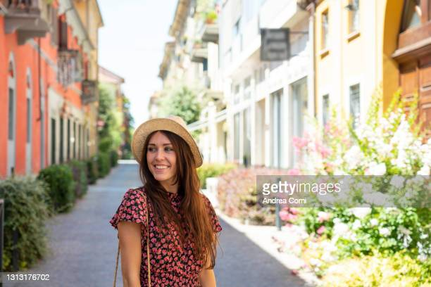 young smiling happy woman among colorful alley in italy - cuneo stock pictures, royalty-free photos & images