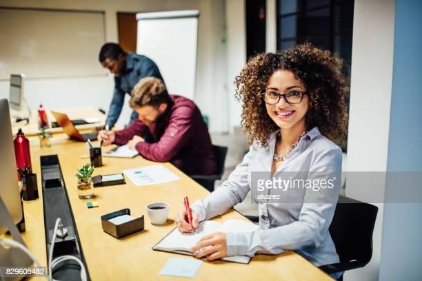 Young smiling hispanic woman working at startup