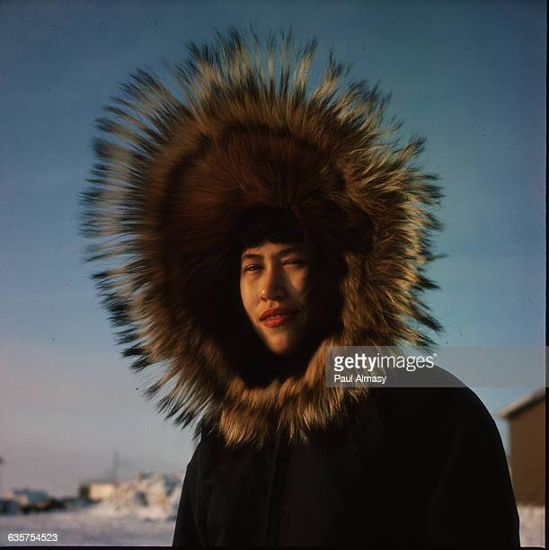 A young smiling Inuit woman in Tutoyaktuk which is in the district of Inuvik Northwest Territories Canada She wears an enormous furlined hood