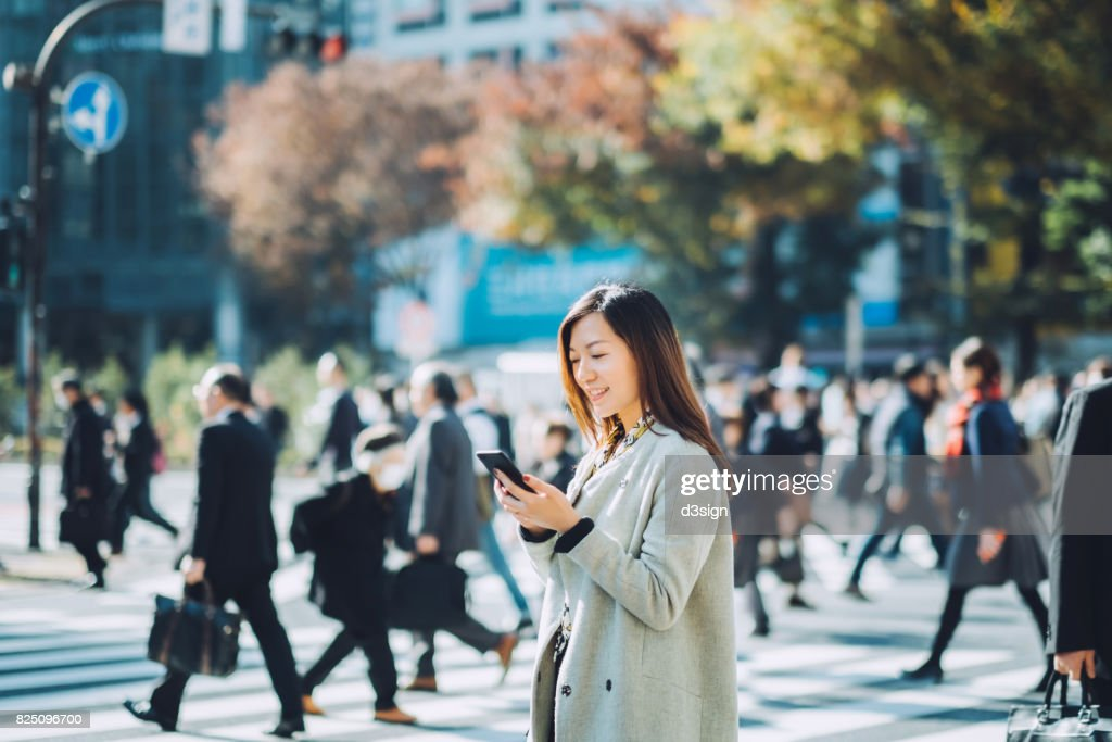 Young smiling lady using smartphone outdoors in busy downtown city street : Stock Photo