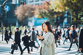 Young smiling lady using smartphone outdoors in busy downtown city street