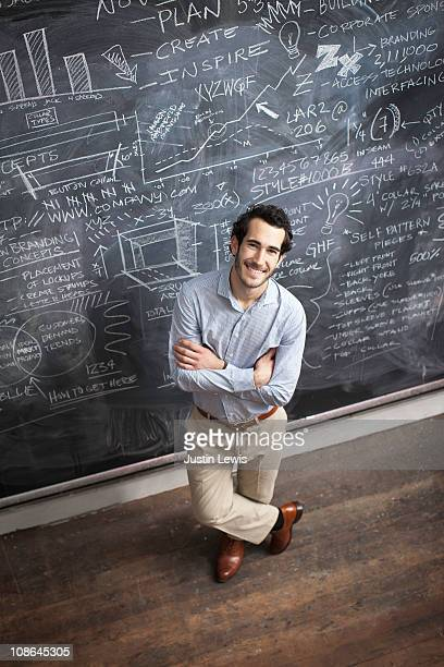 Young smiling male in front of clakboard