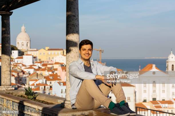 Young smiling man enjoying view of Lisbon skyline at sunset, Portugal