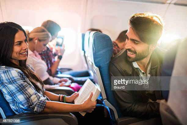 young smiling man flirting with beautiful woman in airplane. - passenger stock pictures, royalty-free photos & images