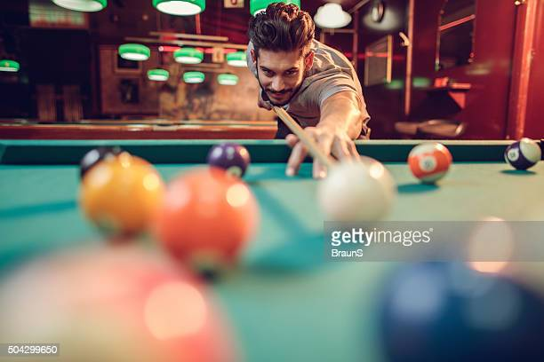 Young smiling man playing snooker in a pub.