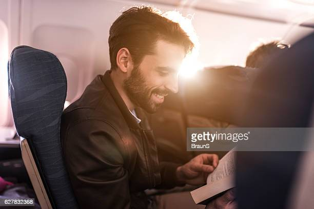 Young smiling man reading a book in the airplane.