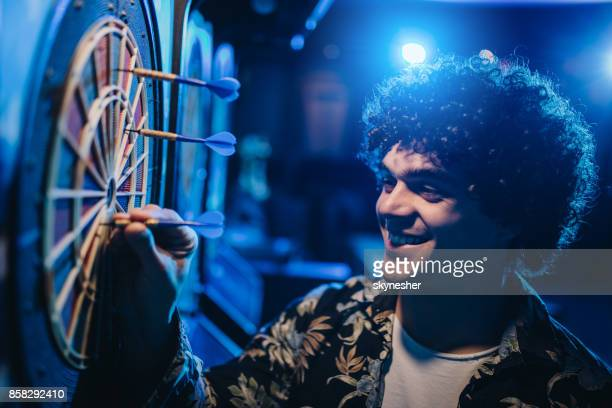 young smiling man removing darts out of dart board in a pub. - dart stock pictures, royalty-free photos & images