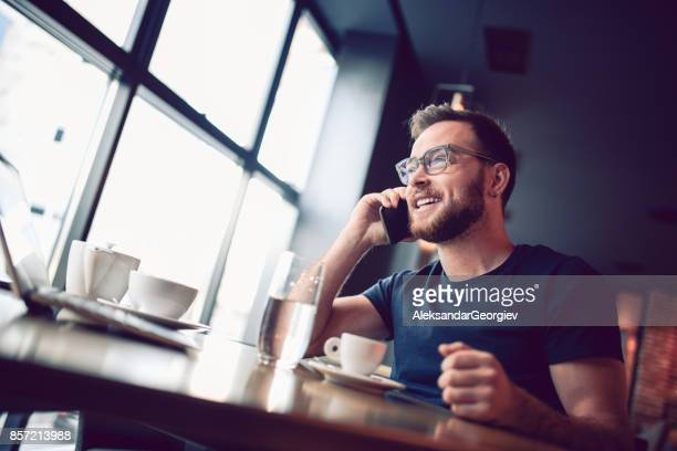 young smiling man talking on mobile phone in cafe restaurant - aleksandar georgiev stock photos and pictures