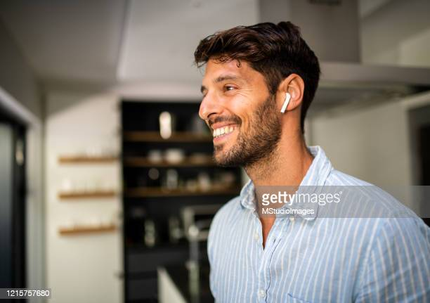 young smiling man using bluetooth earphones. - mid adult men stock pictures, royalty-free photos & images