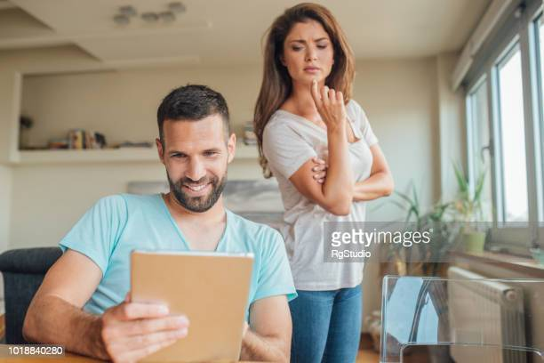 young smiling man using digital tablet and woman looking over his shoulder - boyfriend stock pictures, royalty-free photos & images