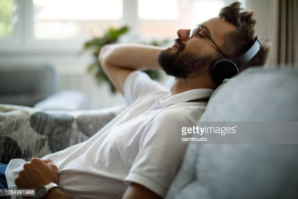 young smiling man with bluetooth headphones relaxing on sofa - resting stock pictures, royalty-free photos & images