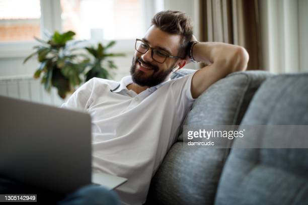 young smiling man with bluetooth headphones using laptop at home - live event stock pictures, royalty-free photos & images